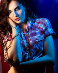 pretty brunette woman wearing dress on dark background