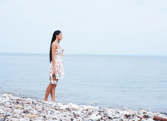 A young woman in a dress on a beautiful sea background