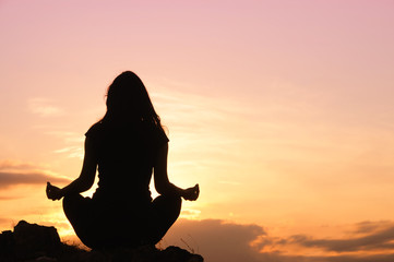 Woman meditation on the top of the hill