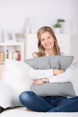 frau sitzt gemütlich auf dem sofa