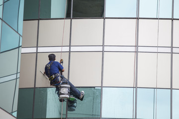 worker cleaning high tower