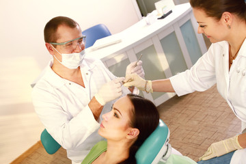 Young woman with dentist in a dental surgery