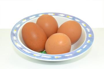 Cuatro huevos morenos en un bol.