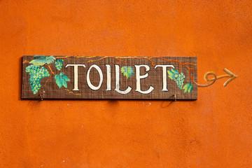 Toilet wood label on the orange wall.