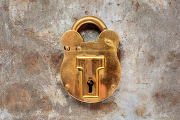 Vintage brass padlock on a steel rusty background