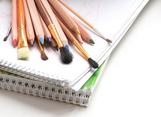 Colored pencils, notepad and paint brushes