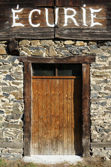 Entrance door to a horse stable with written word Ecurie, France