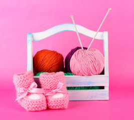 Knitting balls in box on color background