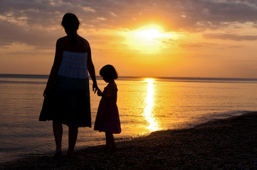 Mother and kid silhouettes on sunset beach, family vacation