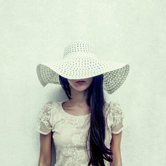 fashion portrait of a sensual girl in a hat against the wall