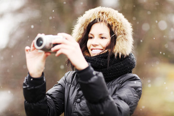 Woman is standing with camera durring wintertime.