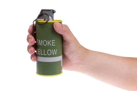 Yellow smoke grenade  in hand isolated on white