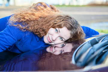 Young woman lying face down on hood of new car