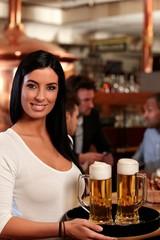 Beautiful waitress serving beer