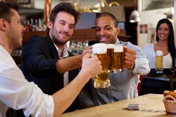 Friends clinking with beer mugs in pub