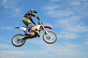 Wall Mural - High flight by motorcycle racer motocross against the blue sky