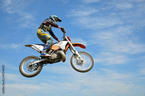 Wall mural High flight by motorcycle racer motocross against the blue sky