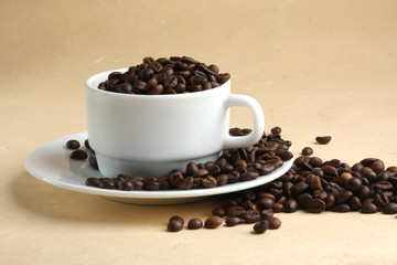 A cup full of coffee beans, isolated on yellow, closeup