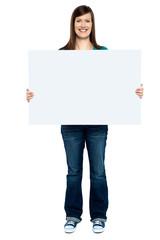 Trendy woman showing blank billboard to camera