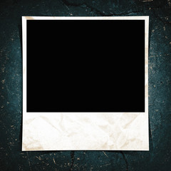 A blank instant photo taped to a grunge background.