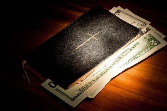 Bibel mit Geldscheinen im Spotlight