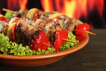 tasty grilled meat and vegetables on plate, on fire background
