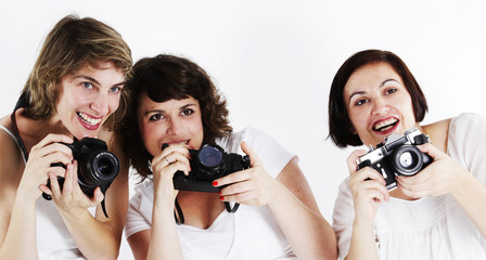 Three women shooting pictures