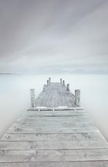 Drewniane molo na jeziorze w pochmurny i mglisty nastrój. - 47399497
