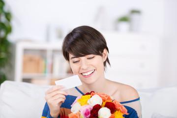 lächelnde frau liest glückwunschkarte