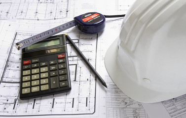 Hard hat, calculator, pencil and tape measure lying on blueprint
