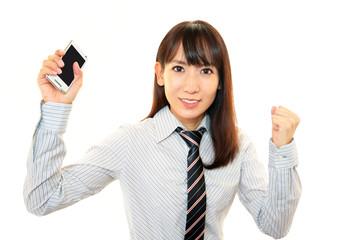 スマートフォンを持ちガッツポーズをするOL