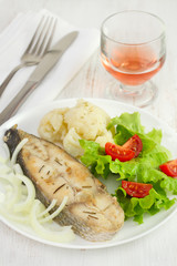 fish with vegetables on the plate and glass of pink wine