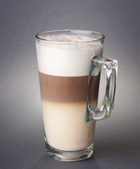 Glass of latte macchiato on the gray background
