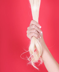 blonde hair in female hand over red background