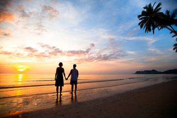 A young couple in love holding at sunset at the seaside