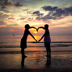 Young couple holding heart-shaped on the beach