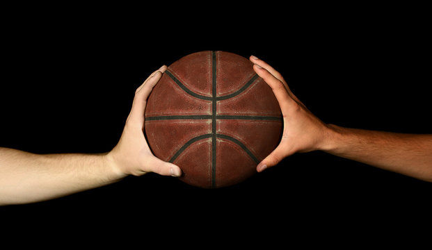 Two hands holding basketball