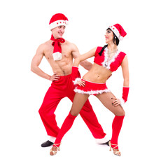 Happy young couple wearing santa claus clothes dancing