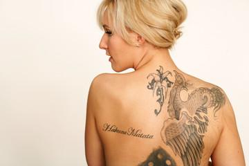 Blonde Frau mit tätowiertem Rücken