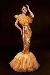 Young brunette lady in golden gorgeous dress posing on black bac