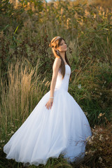 Beautiful lady in wedding dress walking in the countryside