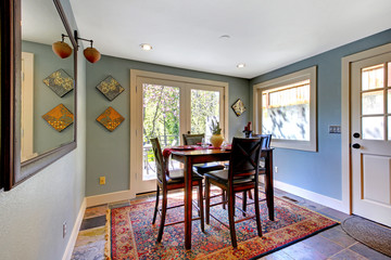 Blue dining room with red rug and high table.