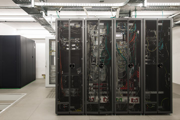 backside of arranged black server racks in small computer room