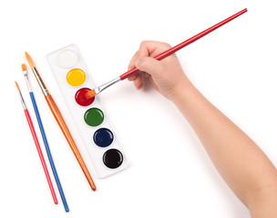 child's hand paints with watercolors and brush