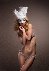A young woman posing in erotic lingerie and a white mask
