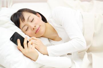スマートフォンを持ったまま寝る女性