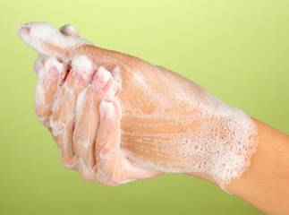 Woman's hands in soapsuds, on green background close-up