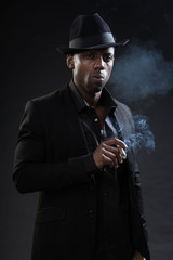 Black man wearing suit and hat gangster style smoking cigar.