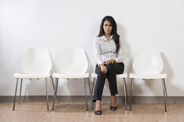 Indian business woman sitting on a row of chairs
