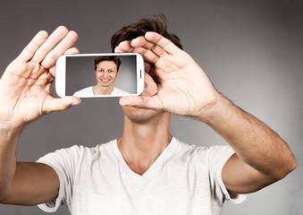 Mann fotografiert sich selbst mit seinem Mobiltelefon